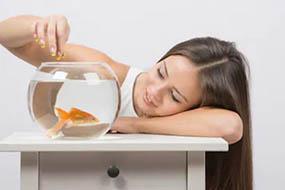 Милая девушка кормит аквариумную рыбку